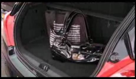 An image of valuables and shopping bags being placed securely in the boot.