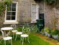 A rear garden with table and chairs and plant pots.
