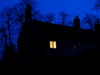 A house at night with a single light on.