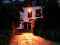 A path leading up to a house with a street light on.